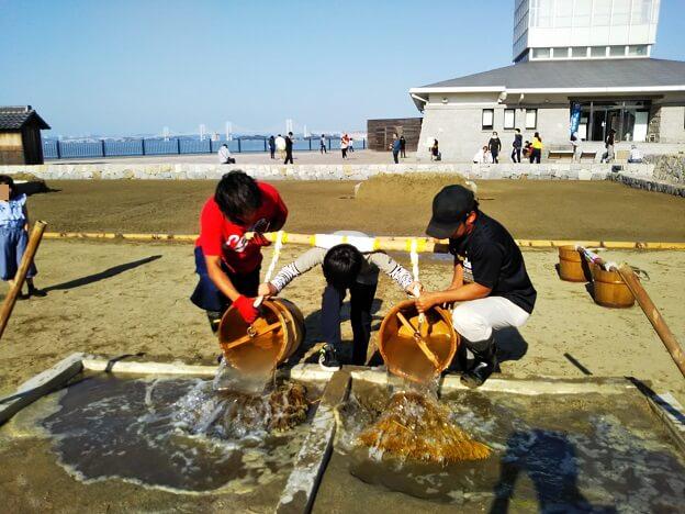 担桶を使って海水を沼井の中に